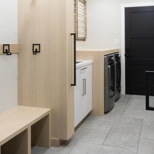 Inspiration för ett mellanstort funkis brun linjärt brunt grovkök, med en undermonterad diskho, släta luckor, skåp i ljust trä, träbänkskiva, grå väggar, kalkstensgolv, en tvättmaskin och torktumlare bredvid varandra och grått golv
