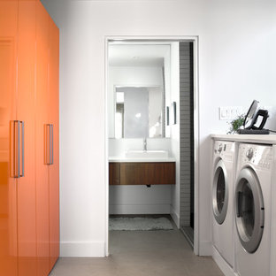 Inspiration for a midcentury galley dedicated laundry room in Other with flat-panel cabinets, orange cabinets, white walls, a side-by-side washer and dryer and white benchtop.