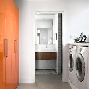Immagine di una sala lavanderia minimalista con ante lisce, ante arancioni, pareti bianche, lavatrice e asciugatrice affiancate e top bianco