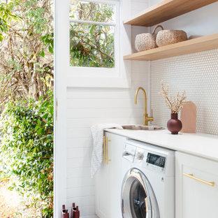 Lantlig inredning av en tvättstuga, med en nedsänkt diskho, vita väggar, en tvättmaskin och torktumlare bredvid varandra och grått golv