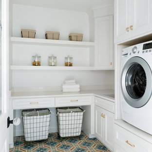 Inspiration for a large transitional l-shaped dedicated laundry room in Minneapolis with an undermount sink, white cabinets, solid surface benchtops, white walls, terra-cotta floors, a side-by-side washer and dryer, blue floor and white benchtop.
