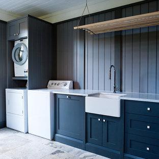 Klassisk inredning av en stor tvättstuga enbart för tvätt, med en rustik diskho, skåp i shakerstil, marmorbänkskiva, grå väggar, travertin golv, en tvättmaskin och torktumlare bredvid varandra och blå skåp