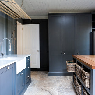 Design ideas for a large traditional u-shaped dedicated laundry room in Sydney with a farmhouse sink, shaker cabinets, grey cabinets, marble benchtops, white splashback, porcelain splashback, travertine floors, grey walls and a concealed washer and dryer.