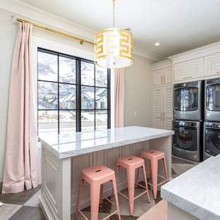 Inspiration for a large transitional l-shaped multicolored floor dedicated laundry room remodel in Salt Lake City with a farmhouse sink, louvered cabinets, a stacked washer/dryer, gray countertops, marble countertops, gray cabinets and gray walls