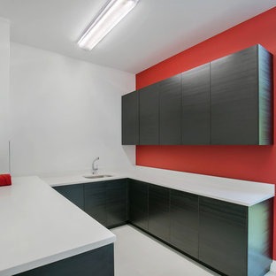 Large modern u-shaped utility room in Tampa with a submerged sink, flat-panel cabinets, dark wood cabinets, engineered stone countertops, red walls, porcelain flooring, a side by side washer and dryer, grey floors and white worktops.