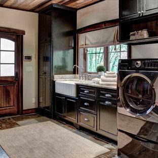 Ispirazione per una lavanderia multiuso stile rurale di medie dimensioni con lavello stile country, ante con bugna sagomata, ante nere, top in granito, pareti beige, pavimento in ardesia e lavatrice e asciugatrice affiancate