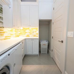 Ispirazione per una sala lavanderia nordica di medie dimensioni con ante in stile shaker, ante bianche, top in laminato, pareti bianche, pavimento in gres porcellanato, lavatrice e asciugatrice affiancate e pavimento grigio