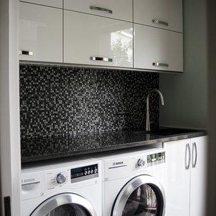 モントリオールの小さいおしゃれな洗濯室 (ドロップインシンク、フラットパネル扉のキャビネット、白いキャビネット、オニキスカウンター、ベージュの壁、左右配置の洗濯機・乾燥機) の写真