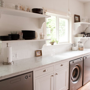 Example of a classic single-wall light wood floor utility room design in Dallas with white cabinets, white walls and white countertops