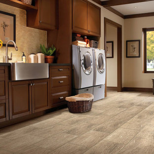 Dedicated laundry room - mid-sized rustic single-wall slate floor dedicated laundry room idea in Denver with a farmhouse sink, raised-panel cabinets, medium tone wood cabinets, beige walls and a side-by-side washer/dryer