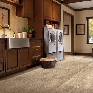 Foto di una sala lavanderia rustica di medie dimensioni con lavello stile country, ante con bugna sagomata, ante in legno scuro, pareti beige, pavimento in ardesia e lavatrice e asciugatrice affiancate