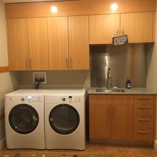 Foto di una lavanderia classica di medie dimensioni con lavello sottopiano, ante lisce, ante in legno scuro, top in superficie solida, pareti beige, pavimento in cemento, lavatrice e asciugatrice affiancate e top grigio