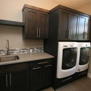 Immagine di una sala lavanderia tradizionale di medie dimensioni con lavello da incasso, ante in stile shaker, ante in legno bruno, top in superficie solida, pareti beige, lavatrice e asciugatrice affiancate, pavimento in gres porcellanato, pavimento beige e top grigio