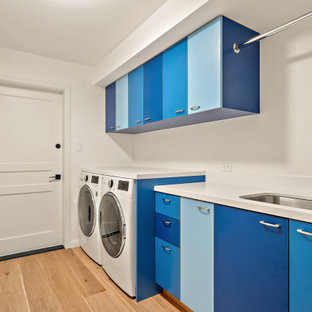 Inspiration for a mid-sized midcentury single-wall dedicated laundry room in San Francisco with an undermount sink, flat-panel cabinets, blue cabinets, solid surface benchtops, white splashback, white walls, laminate floors, a side-by-side washer and dryer, brown floor and white benchtop.