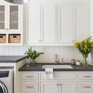 Ispirazione per una grande sala lavanderia con lavello sottopiano, ante con riquadro incassato, ante bianche, top in cemento, pareti bianche, lavatrice e asciugatrice affiancate e top grigio