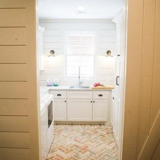 Ispirazione per una sala lavanderia country di medie dimensioni con lavello sottopiano, ante con riquadro incassato, ante bianche, pareti bianche, pavimento in mattoni, lavatrice e asciugatrice affiancate, pavimento beige, top in cemento e top grigio