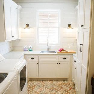 Ispirazione per una sala lavanderia country di medie dimensioni con lavello sottopiano, ante con riquadro incassato, ante bianche, pareti bianche, pavimento in mattoni, lavatrice e asciugatrice affiancate, pavimento beige, top grigio e top in cemento