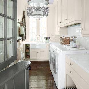 Esempio di una lavanderia classica con ante beige, lavello stile country, pavimento marrone e top bianco