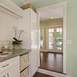 Immagine di una lavanderia tradizionale con ante in stile shaker, ante bianche, pareti verdi, parquet scuro, lavatrice e asciugatrice affiancate e top verde