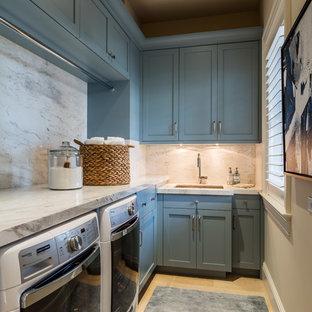 Foto på en vintage vita l-formad tvättstuga enbart för tvätt, med en undermonterad diskho, skåp i shakerstil, blå skåp, beige väggar, ljust trägolv och en tvättmaskin och torktumlare bredvid varandra