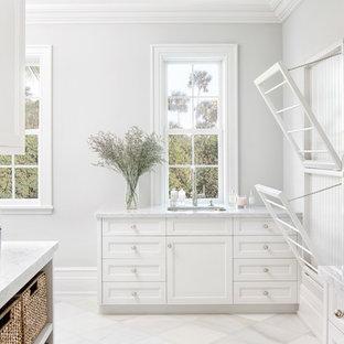 Idées déco pour une buanderie bord de mer dédiée avec un évier encastré, un placard à porte shaker, des portes de placard blanches, un mur gris, un sol blanc et un plan de travail gris.