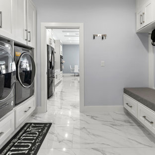 Inspiration for a mid-sized coastal white floor dedicated laundry room remodel in Jacksonville with shaker cabinets, white cabinets, a side-by-side washer/dryer and gray walls