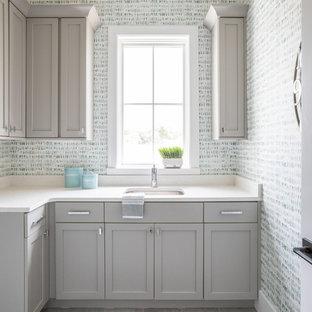 Cette photo montre une buanderie bord de mer en L dédiée avec un évier encastré, un placard à porte shaker, des portes de placard grises, un mur multicolore, un sol gris et un plan de travail blanc.