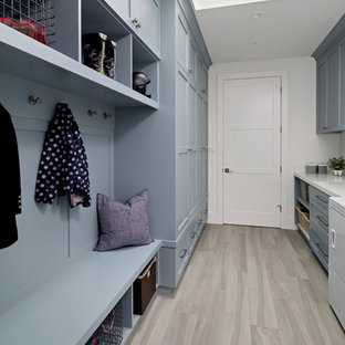 Inspiration for a large country galley utility room in San Francisco with a built-in sink, shaker cabinets, blue cabinets, composite countertops, white walls, medium hardwood flooring, a side by side washer and dryer, grey floors and white worktops.
