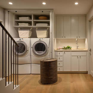 Design ideas for a mid-sized transitional single-wall dedicated laundry room in San Francisco with an undermount sink, recessed-panel cabinets, grey cabinets, limestone benchtops, grey walls, medium hardwood floors, a side-by-side washer and dryer and beige benchtop.