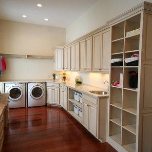 Immagine di una grande lavanderia multiuso mediterranea con lavello sottopiano, ante con bugna sagomata, ante beige, top in granito, pareti beige, parquet scuro, lavatrice e asciugatrice affiancate e pavimento rosso