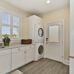 Immagine di una lavanderia multiuso minimalista di medie dimensioni con lavello sottopiano, ante a persiana, ante bianche, top in granito, lavatrice e asciugatrice a colonna e top beige