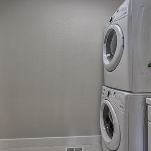 Foto di una sala lavanderia tradizionale con ante con riquadro incassato, ante bianche, top piastrellato, pareti beige, pavimento in gres porcellanato, lavatrice e asciugatrice a colonna e pavimento beige