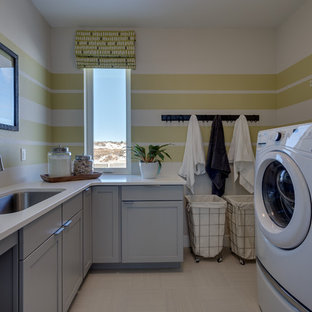 Inspiration for a 1950s u-shaped porcelain floor and beige floor laundry room remodel in Denver with an undermount sink, shaker cabinets, gray cabinets, quartz countertops and yellow walls