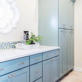 Inspiration för en stor medelhavsstil parallell tvättstuga enbart för tvätt, med en undermonterad diskho, skåp i shakerstil, blå skåp, bänkskiva i kvarts, vita väggar, travertin golv och en tvättmaskin och torktumlare bredvid varandra