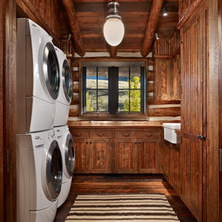 Inspiration for a mid-sized rustic dark wood floor and brown floor dedicated laundry room remodel in Other with a farmhouse sink, shaker cabinets, dark wood cabinets, wood countertops, brown walls, a stacked washer/dryer and brown countertops