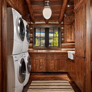 Esempio di una sala lavanderia rustica di medie dimensioni con lavello stile country, ante in stile shaker, ante in legno bruno, top in legno, pareti marroni, parquet scuro, lavatrice e asciugatrice a colonna, pavimento marrone e top marrone