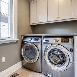Inredning av en klassisk mellanstor linjär tvättstuga enbart för tvätt, med en undermonterad diskho, skåp i shakerstil, vita skåp, bänkskiva i zink, beige väggar, klinkergolv i porslin och en tvättmaskin och torktumlare bredvid varandra