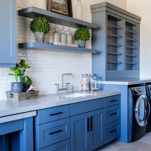 Ispirazione per una grande lavanderia multiuso american style con lavello da incasso, ante in stile shaker, ante blu, top in quarzo composito, pareti bianche, pavimento in pietra calcarea, lavatrice e asciugatrice affiancate, pavimento grigio e top grigio