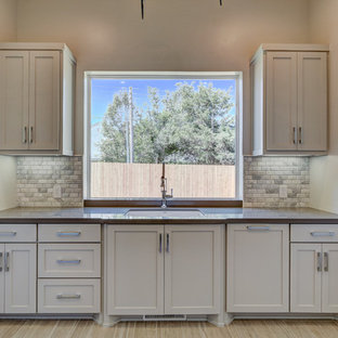 Design ideas for a mid-sized contemporary u-shaped dedicated laundry room in Oklahoma City with an undermount sink, recessed-panel cabinets, stainless steel cabinets, quartzite benchtops, grey walls, light hardwood floors and a side-by-side washer and dryer.