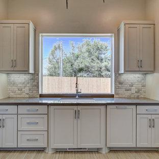 Foto på en mellanstor funkis u-formad tvättstuga enbart för tvätt, med en undermonterad diskho, luckor med infälld panel, skåp i rostfritt stål, bänkskiva i kvartsit, grå väggar, ljust trägolv och en tvättmaskin och torktumlare bredvid varandra