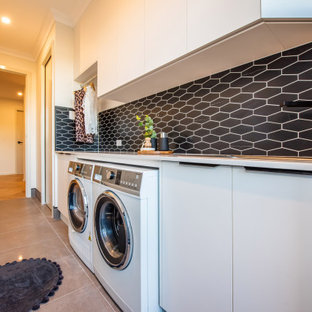 Photo of a mid-sized contemporary single-wall dedicated laundry room in Other with a single-bowl sink, flat-panel cabinets, white cabinets, granite benchtops, black splashback, mosaic tile splashback, white walls, ceramic floors, a side-by-side washer and dryer, grey floor and white benchtop.