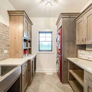 Mid-sized country dedicated laundry room in Chicago with a farmhouse sink, shaker cabinets, distressed cabinets, quartz benchtops, beige splashback, brick splashback, white walls, ceramic floors, a stacked washer and dryer, grey floor, white benchtop and brick walls.