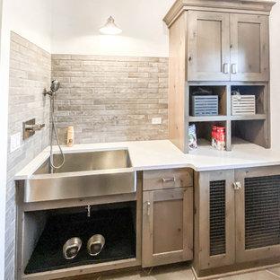Industriell inredning av en mellanstor vita vitt tvättstuga enbart för tvätt, med en rustik diskho, skåp i shakerstil, skåp i slitet trä, bänkskiva i kvarts, beige stänkskydd, stänkskydd i tegel, vita väggar, klinkergolv i keramik, en tvättpelare och grått golv
