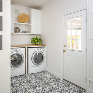 Example of a mid-sized cottage porcelain tile and multicolored floor utility room design in Raleigh with a farmhouse sink, white cabinets, quartzite countertops, white walls, a side-by-side washer/dryer and brown countertops