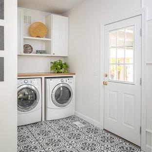 Idéer för mellanstora lantliga brunt grovkök, med en rustik diskho, vita skåp, bänkskiva i kvartsit, vita väggar, klinkergolv i porslin, en tvättmaskin och torktumlare bredvid varandra och flerfärgat golv