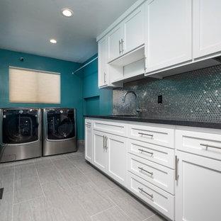 Immagine di una grande sala lavanderia contemporanea con lavello sottopiano, ante in stile shaker, ante bianche, top in granito, pareti verdi, pavimento in gres porcellanato, lavatrice e asciugatrice affiancate, pavimento grigio e top nero