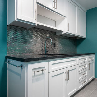 Design ideas for a large contemporary l-shaped separated utility room in San Francisco with a submerged sink, shaker cabinets, white cabinets, granite worktops, porcelain flooring, a side by side washer and dryer, grey floors, black worktops and blue walls.