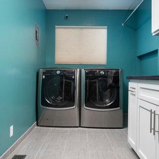 Idee per una grande sala lavanderia contemporanea con lavello sottopiano, ante in stile shaker, ante bianche, top in granito, pavimento in gres porcellanato, lavatrice e asciugatrice affiancate, pavimento grigio, top nero e pareti blu
