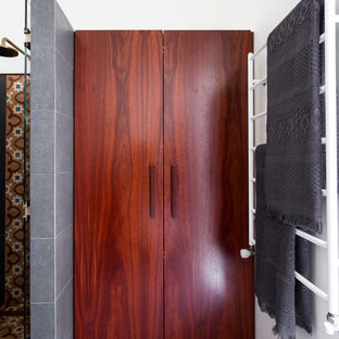 Idee per una piccola lavanderia multiuso boho chic con ante in legno bruno, pavimento in gres porcellanato e lavatrice e asciugatrice nascoste
