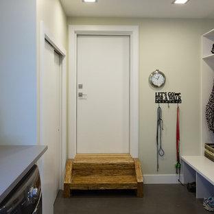 Foto di una grande lavanderia multiuso minimalista con top in quarzite, pareti beige, lavatrice e asciugatrice affiancate, pavimento marrone e top grigio